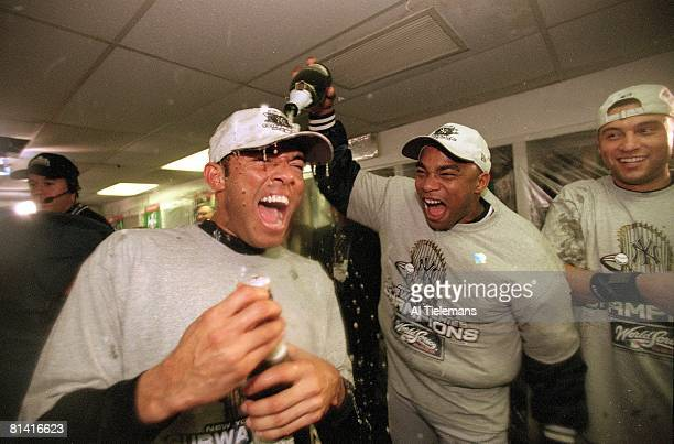 Baseball World Series New York Yankees Orlando Hernandez in locker room victorious pouring champagne on Mariano Rivera after winning game and series...