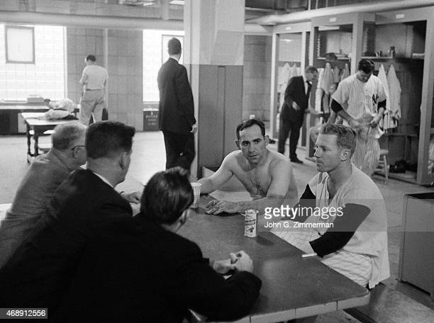 World Series New York Yankees Yogi Berra and Whitey Ford with reporters in locker room after losing Game 7 and championship series to Milwaukee...