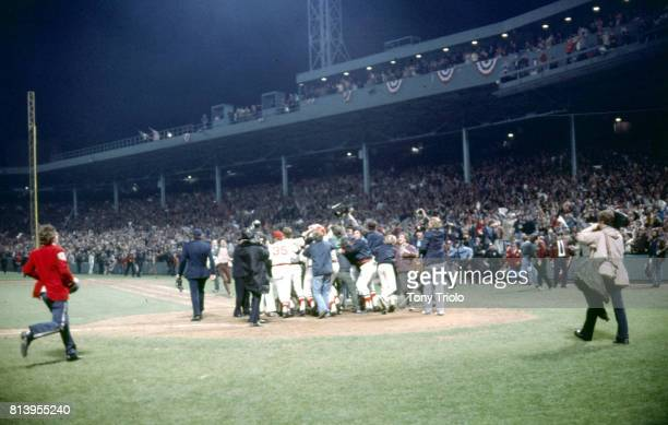 World Series Rear view of Boston Red Sox Carlton Fisk victorious with teammates after hitting game winning walk off home run vs Cincinnati Reds in...