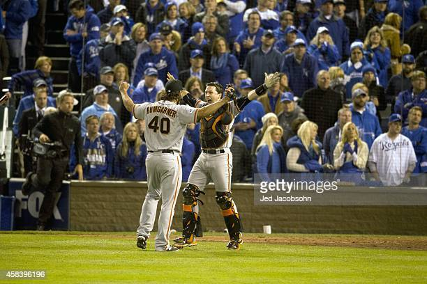 World Series Rear view of San Francisco Giants Madison Bumgarner victorious with Buster Posey after winning Game 7 and championship series vs Kansas...