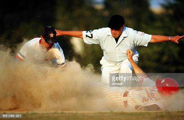 baseball,player diving for base in cloud of dust,watched by umpire - 線審 ストックフォトと画像