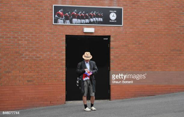 Basel fan waits outside the ground by the Munich Air Disaster Memorial prior to the UEFA Champions League group A match between Manchester United and...