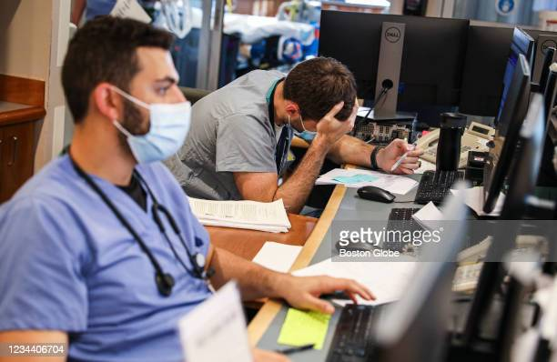 Basel Humos, left, and MD Benjamin Schwartz work behind the desk in the Medical Intensive Care Unit at Tufts Medical Center in Boston on July 29,...