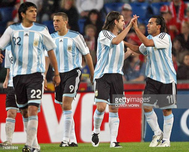 Argentina's Carlos Tevez is congratulated by his teammates after scoring against Switzerland goalie Diego Benaglio 02 June 2007 during their friendly...