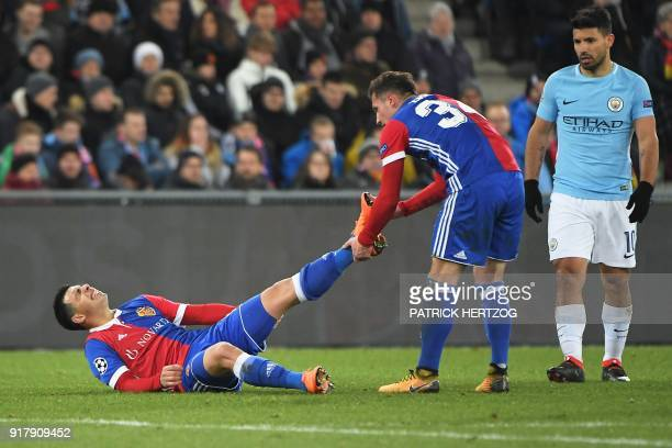 Basel's Albanian midfielder Taulant Xhaka helps Basel's Paraguayan defender Blas Riveros to stretch during the UEFA Champions League round of 16...