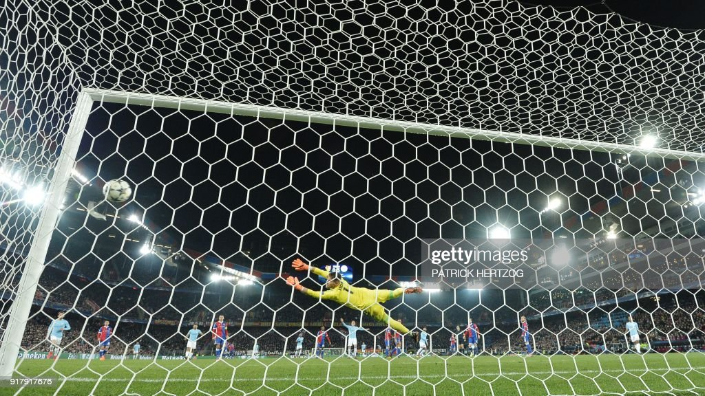 Basel's Czech goalkeeper Tomas Vaclik (C) dives and takes a fourth goal scored by Manchester City's German midfielder Ilkay Gundogan (C-R) during the UEFA Champions League round of 16 first leg football match between Basel and Manchester City at the Saint Jakob-Park Stadium in Basel on February 13, 2018. /