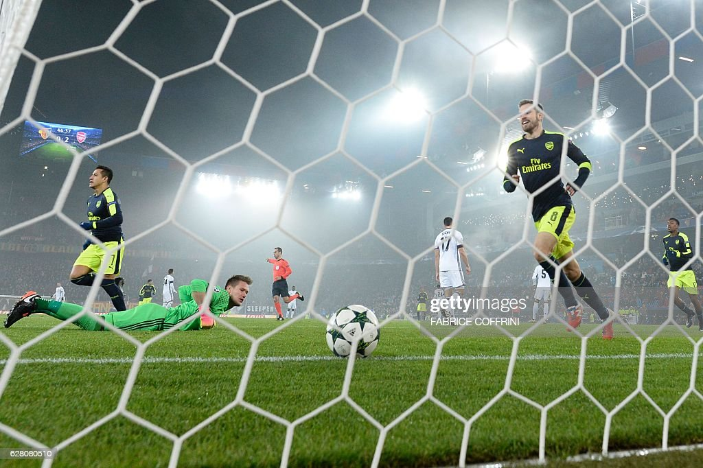 Basel's Czech goalkeeper Tomas Vaclik (2ndL) reacts after the second goal scored by Arsenal as Arsenal's players celebrate during the UEFA Champions league Group A football match between FC Basel 1893 and Arsenal FC on December 6, 2016 at the St Jakob Park stadium in Basel. / AFP / FABRICE