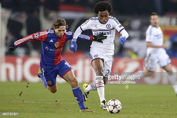 Basel's defender Kay Voser vies with Chelsea's Brazilian midfielder Willian during an UEFA Champions League group E football match FC Basel against...