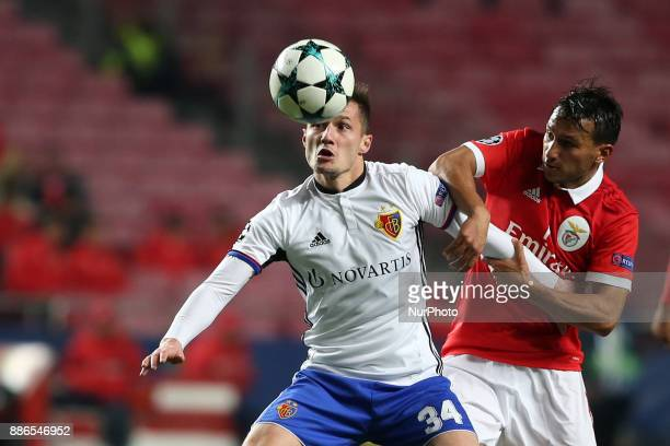 Basel's midfielder Taulant Xhaka from Albania fights for the ball with Benfica's Portuguese midfielder Joao Carvalho during the UEFA Champions League...