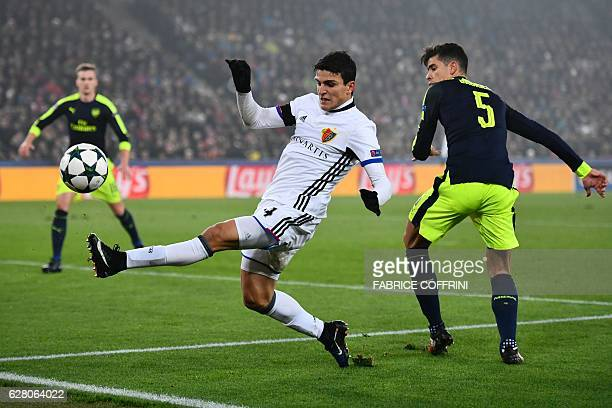 Basel's Norwegian forward Mohamed Elyounoussi after scoring a goal vies with Arsenal's Brazilian defender Gabriel during the UEFA Champions league...
