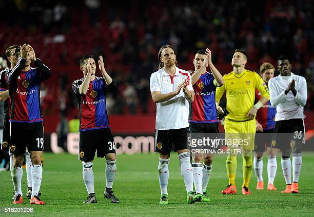 Basel's players applaud their fans at the end of the UEFA Europa League round of 16 second leg football match between Sevilla FC vs FC Basel 1893 at...