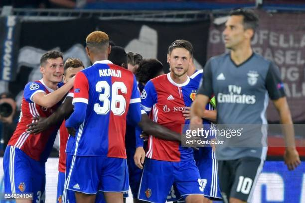 FC Basel's players celebrate a goal as Benfica's Brazilian forward Jonas walks past during the UEFA Champions League Group A football match between...