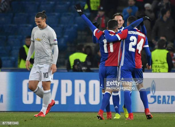 Basel's players celebrate as Manchester United's Swedish forward Zlatan Ibrahimovic reacts the UEFA Champions League Group A football match between...
