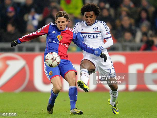 Basel's Swiss defender Kay Voser vies for the ball with Chelsea's Brazilian midfielder Willian during the UEFA Champions League group E football...