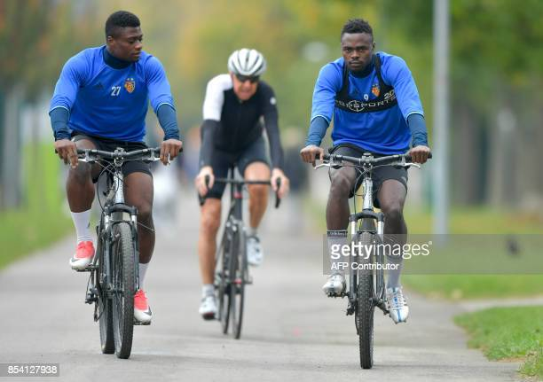 Basel's Swiss forward Neftali Manzambi and Basel's Swiss forward Dimitri Oberlin arrive on bicycle to a training session on the eve of the UEFA...