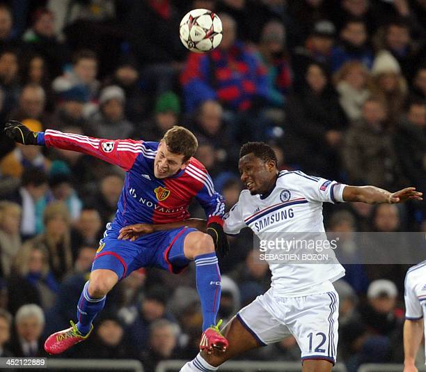 Basel's Swiss midfielder Fabian Frei jumps for the ball with Chelsea's Nigerian midfielder John Mikel Obi during the UEFA Champions League group E...