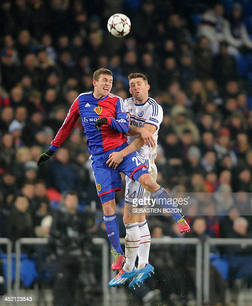 Basel's Swiss midfielder Fabian Frei jumps for the ball with Chelsea's English defender Gary Cahill during the UEFA Champions League group E football...
