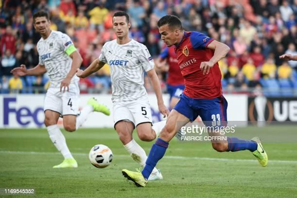 Basel's Swiss midfielder Kevin Bua fights for the ball with FK Krasnodar's Belarussian defender Alyaksandr Martynovich and FK Krasnodar's Serbian...
