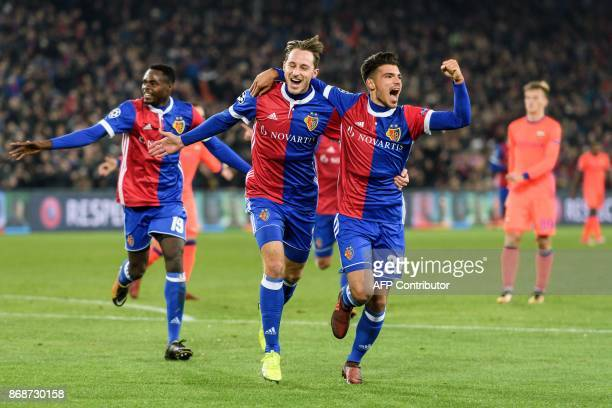 Basel's Swiss midfielder Luca Zuffi celebrates with teammates Italian defender Raoul Petretta after scoring a goal during the UEFA Champions League...