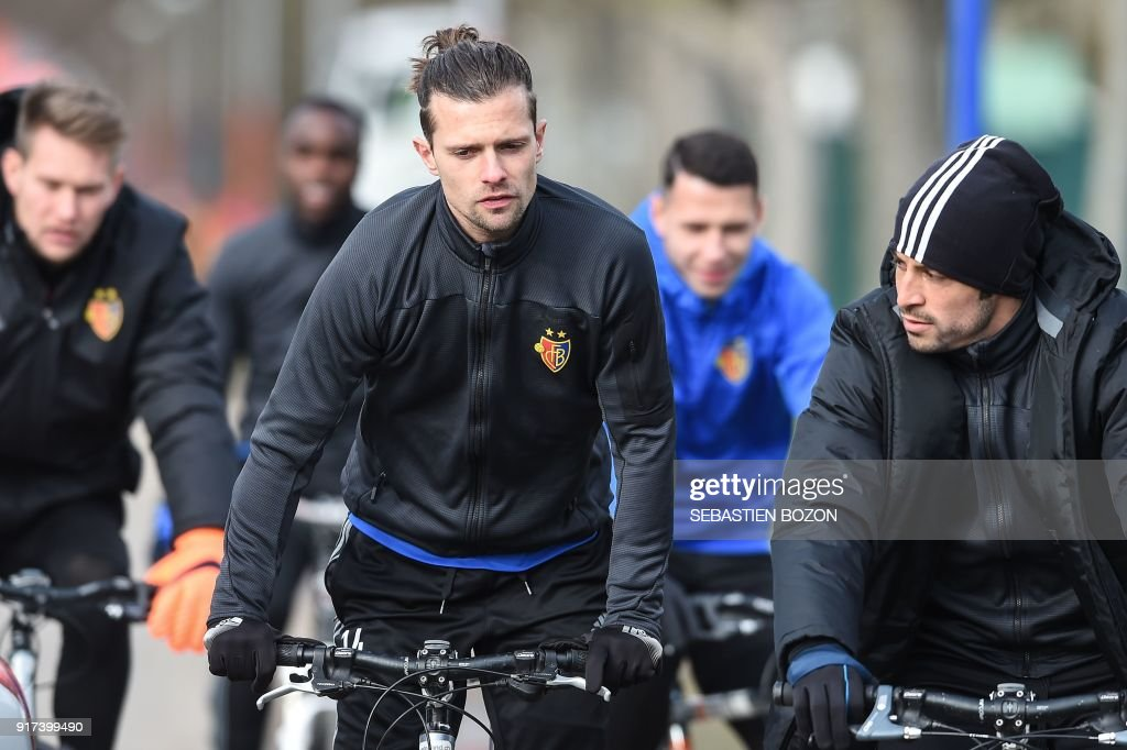 Basel's Swiss midfielder Valentin Stocker (C) rides a bike as he arrives for a training session on February 12, 2018, in Basel, on the eve of the UEFA Champions League round of 16 football between Basel and Manchester City. /