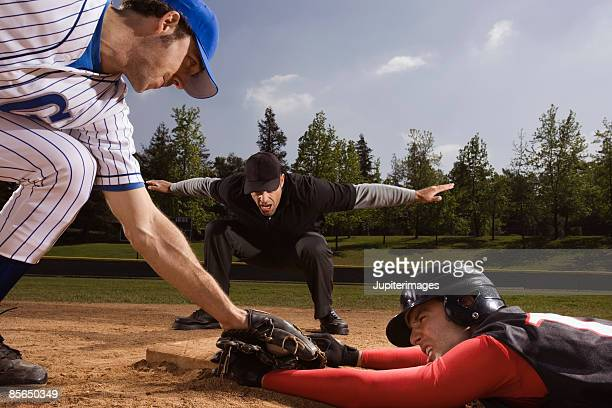 Baseman trying to strike out baseball player while umpire signals him safe