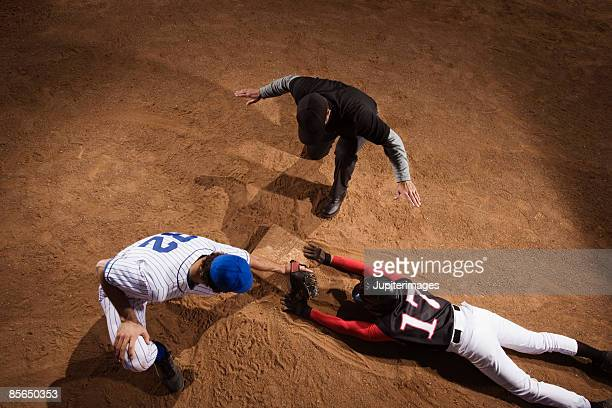 baseman trying to strike out baseball player while umpire signals him safe - 線審 ストックフォトと画像