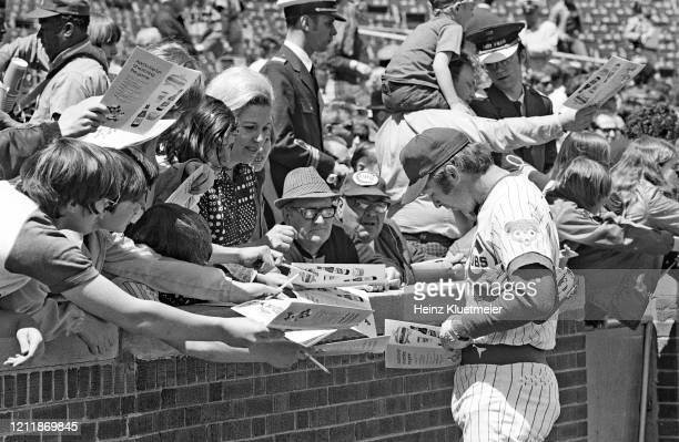Chicago Cubs Glenn Beckert signings autographs for fans in stands before game vs New York Mets at Wrigley Field Chicago IL CREDIT Heinz Kluetmeier
