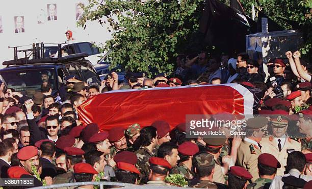 Bashar alAssad son and successor of the late President walking behind his father's coffin raises his fist to greet the crowd