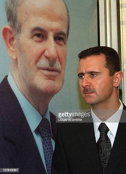 Bashar alAssad son of Syrian President Hafez alAssad stands under a portrait of his father 24 April 2000 in Damascus