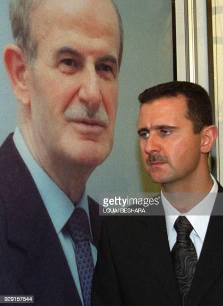 Bashar alAssad son of Syrian President Hafez alAssad stands under a portrait of his father 24 April 2000 in Damascus / AFP PHOTO / LOUAI BESHARA