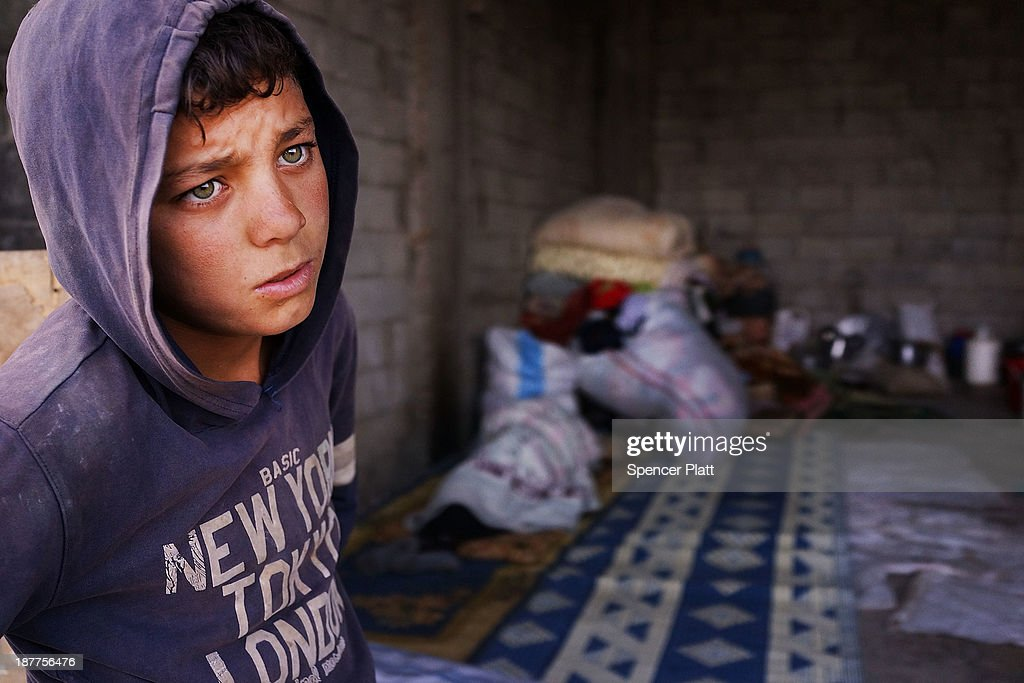 Bashar, an 11 year old Syrian refugee, stands near an empty garage he shares with members of his family only miles from the border with Syria in the Bekaa Valley on November 12, 2013 in Majdal Anjar, Lebanon. As the war in neighboring Syria drags on for a third year, Lebanon, a country of only 4 million people, is now home to the largest number of Syrian refugees who have fled the conflict. The situation is beginning to put huge social and political strains on Lebanon as there is currently no end in sight to the war in Syria.