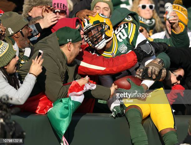 Bashaud Breeland of the Green Bay Packers celebrates with fans after returning an interception for a touchdown during the first half of a game...