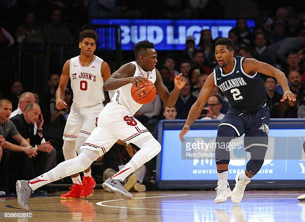 Bashir Ahmed of the St Johns Red Storm drives to the basket as Kris Jenkins of the Villanova Wildcats defends during the first half of an NCAA...