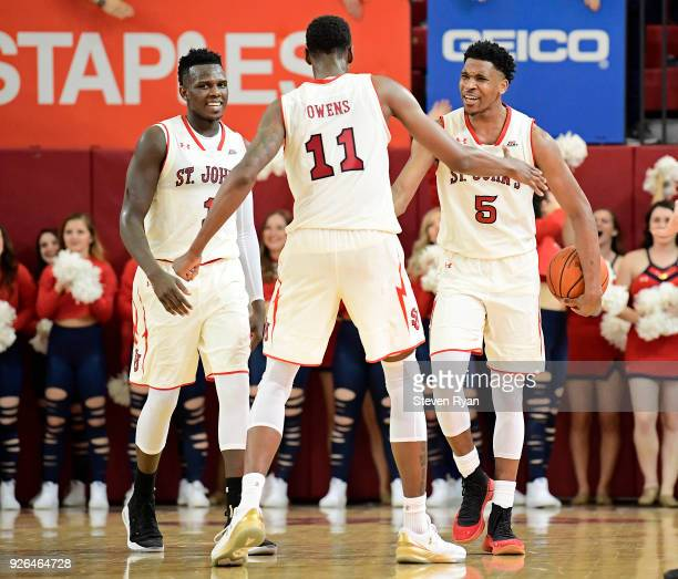 Bashir Ahmed Tariq Owens and Justin Simon of the St John's Red Storm celebrate their teams lead against the Butler Bulldogs during an NCAA basketball...
