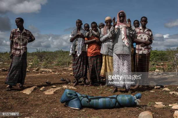 Bashir Bille stands by the body of his son Noor Bashir as men pray prior to his burial at the Mogor I Maanyi IDP camp in Baidoa Somalia on May 13...