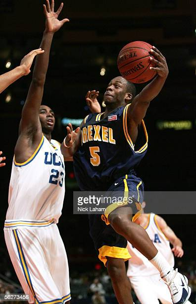 Bashir Mason of the Drexel Dragons goes in for a layup in front of Luc Richard Mbah a Moute of the UCLA Bruins during their Preseason NIT Tournament...