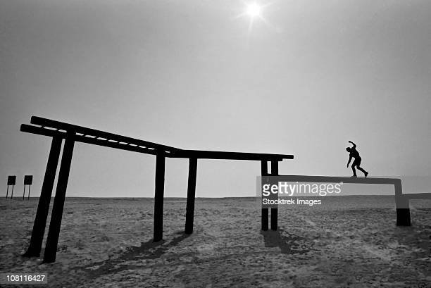 a basic underwater demolition seal student maintains balance while walking across a balance beam. - obstacle course stock pictures, royalty-free photos & images