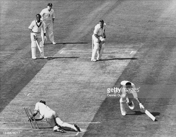 Basil Butcher of the West Indies reaches to make the crease as Tony Lock of England knocks down the stumps in a run out attempt during the first...