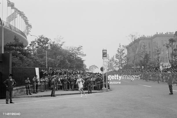 Basil Heatley of Great Britain enters the stadium to take second place and the silver medal at the Men's Marathon race on 21st October 1964 during...