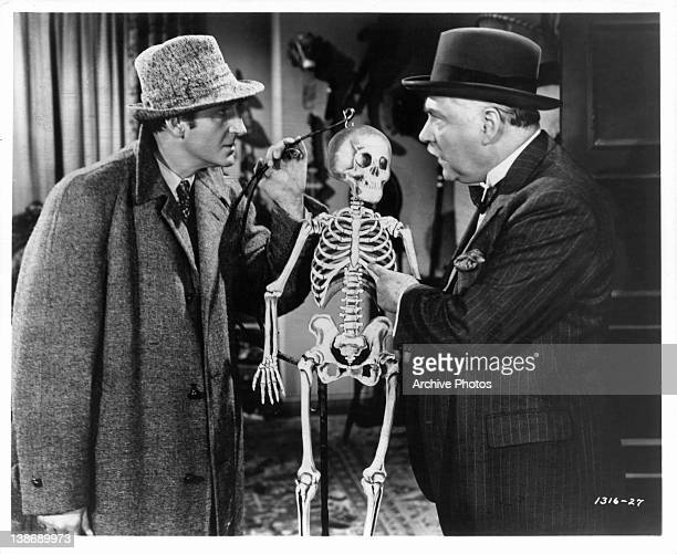 Basil Rathbone and Nigel Bruce holding skeleton in a scene from the film 'The Spider Woman' 1944