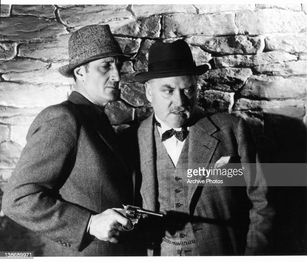 Basil Rathbone holding gun with Nigel Bruce in a scene from the film 'The Scarlet Claw' 1944