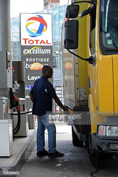 Basile William fills his truck with fuel at a Total SA gas station in Paris France on Thursday July 22 2010 The company Europe's biggest oil refiner...