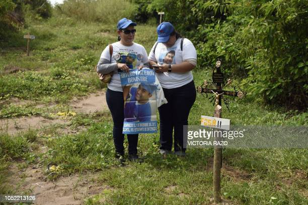 Basilia Bonastre and her daughter cry over the grave where her son and brother Arturo Figueroa Bonastre was found during a mass at the pits called...