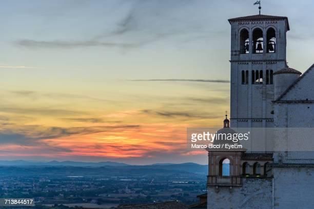 basilica of san francisco amidst town against cloudy sky during sunset - basilica stock pictures, royalty-free photos & images