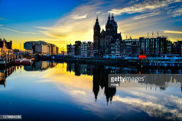 basilica of st. nicholas with morning reflections on the amstel river - amsterdam netherlands - st. nicholas cathedral stock pictures, royalty-free photos & images