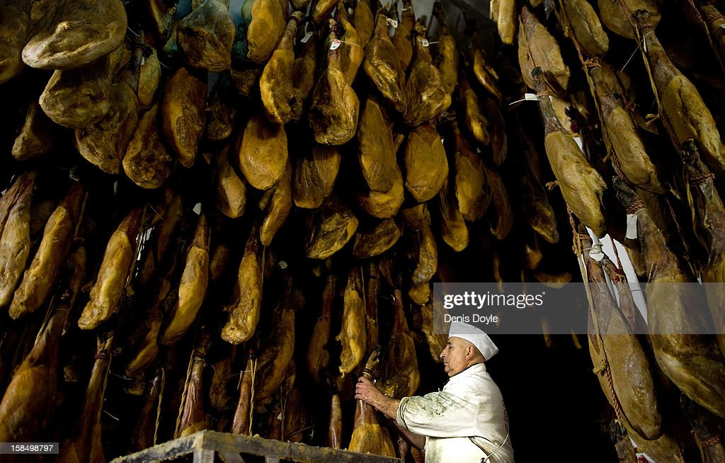 Basilio Hoyos, manager of the Sociedad Chacinera Albercana Cooperative checks a leg of dry-cured Jamon Iberico de bellota (acorns) in the village of La Alberca on December 14, 2012 near Salamanca, Spain. Dry-cured Iberian ham or Jamon Iberico de Bellota is a favourite amongst Spaniards and producers are hoping for improved sales over the busy christmas period. The jamon Iberico de Bellota are usually dry-cured for up to three years after the pigs have been few on a diet of acorns in the last three months of their lives.