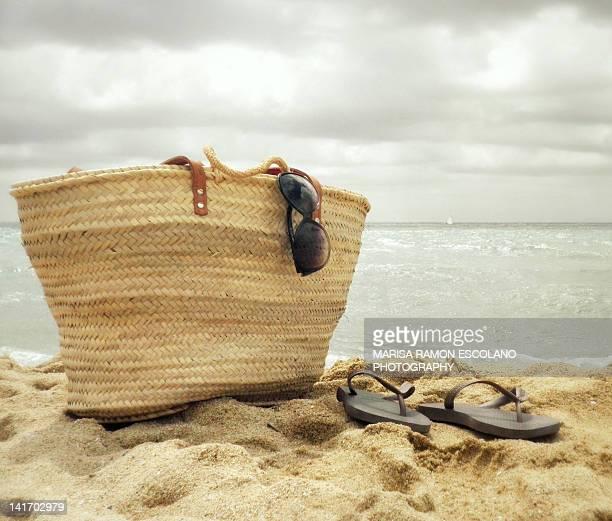 Basket and flip-flops on beach