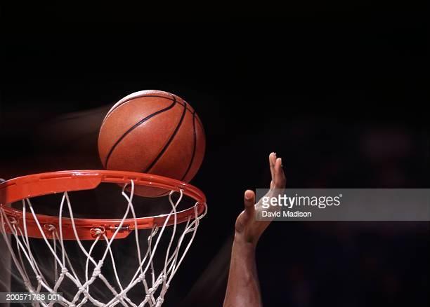 Basket ball player putting ball in net