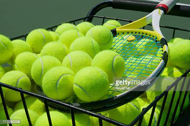 Basket full of tennis balls and a tennis racket