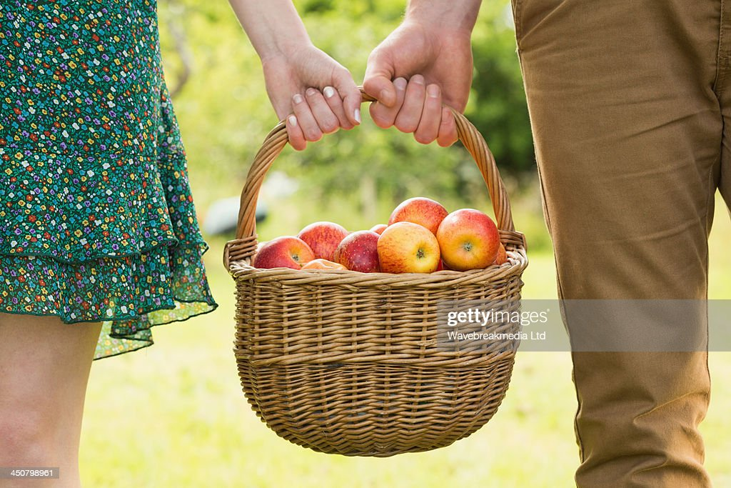 Basket of apples being carried by a young couple : ストックフォト